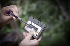 As mulheres rebobinam uma gaveta do estojo compacto do vintage da cassete de banda magnética no fundo do borrão, fim acima do gru imagem de stock