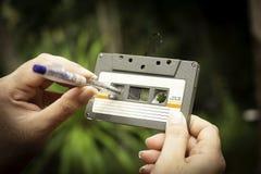 As mulheres rebobinam uma gaveta do estojo compacto do vintage da cassete de banda magnética no fundo do borrão, fim acima do gru foto de stock royalty free