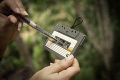 As mulheres rebobinam uma gaveta do estojo compacto do vintage da cassete de banda magnética no fundo do borrão, fim acima do gru fotos de stock royalty free