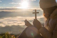 As mulheres rezam ao deus com a cruz no fundo da montanha com nascer do sol da manhã A mulher reza para o deus que a bênção ao de foto de stock royalty free