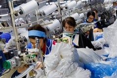 As mulheres são contratadas na costura das calças justas Fotografia de Stock
