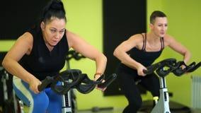 As mulheres são contratadas no treinamento da bicicleta do grupo manter a aptidão física video estoque