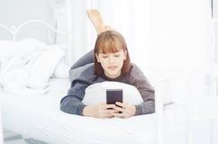 As mulheres são de descanso e de jogo telefones celulares fotografia de stock