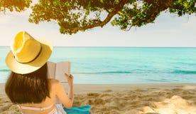 As mulheres sentam-se e lendo um livro sob a árvore no beira-mar Opinião traseira a mulher asiática 'sexy' com o chapéu de palha  fotografia de stock