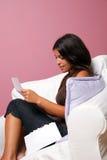 As mulheres sentaram-se em uma poltrona que lêem uma letra foto de stock