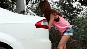As mulheres 'sexy' seridas ao carro e abrem o tronco video estoque