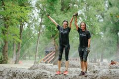 As mulheres superam a barreira da lama da água durante a corrida da legião da raça do poder, realizada em Kiev imagem de stock royalty free