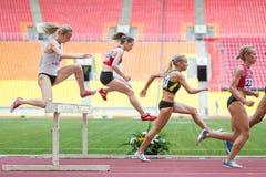 As mulheres superam o obstáculo na competição atlética internacional Foto de Stock Royalty Free