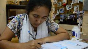 As mulheres tailandesas do desenhista que tiram e a forma do teste padrão do projeto no papel para fazem a placa do humor video estoque