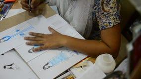 As mulheres tailandesas do desenhista que tiram e a forma do teste padrão do projeto no papel para fazem a placa do humor vídeos de arquivo