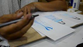 As mulheres tailandesas do desenhista que tiram e a forma do teste padrão do projeto no papel para fazem a placa do humor filme