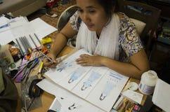 As mulheres tailandesas do desenhista que tiram e a forma do teste padrão do projeto no papel para fazem a placa do humor Fotografia de Stock Royalty Free