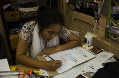As mulheres tailandesas do desenhista que tiram e a forma do teste padrão do projeto no papel para fazem a placa do humor Fotos de Stock Royalty Free