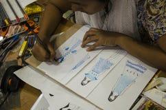 As mulheres tailandesas do desenhista que tiram e a forma do teste padrão do projeto no papel para fazem a placa do humor Fotografia de Stock