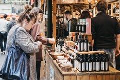 As mulheres tentam o azeite e o vinagre em uma tenda do mercado no mercado da cidade, Londres, Reino Unido imagens de stock royalty free