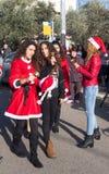 As mulheres vestiram-se em Santa Claus cumprimentaram participantes do Natal R Imagem de Stock