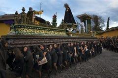 As mulheres vestiram-se no preto que leva um flutuador gigante em uma rua da cidade velha de Antígua durante uma procissão da Sem Fotos de Stock