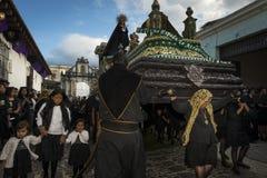 As mulheres vestiram-se no preto que leva um flutuador gigante em uma rua da cidade velha de Antígua durante uma procissão da Sem Fotografia de Stock Royalty Free