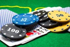 As multi microplaquetas de pôquer coloridas redondas encontram-se em uma plataforma de cartões Imagem de Stock Royalty Free