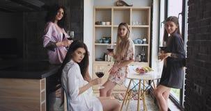 As multi senhoras étnicas em surpreender pijamas à moda apreciam o tempo junto em um projeto moderno do apartamento que guarda vi filme