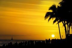 As multidões de turistas recolhem para olhar o por do sol na praia Honolulu Oahu Havaí EUA de Waikiki fotografia de stock