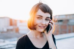 As negociações bonitas novas da mulher no telefone olham in camera Fotografia de Stock