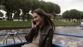 As negociações da jovem mulher no telefone em um rio visitam, sightseeing, sorrindo felizmente O vento está fundindo seu cabelo M video estoque