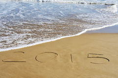 2015, as the new year, written on the sand of a beach. The number 2015, as the new year, written in the sand of a beach royalty free stock images