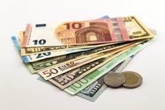 As notas de dólar dos E.U. e as contas do Euro espalharam misturado no fundo branco Imagens de Stock