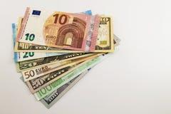 As notas de dólar dos E.U. e as contas do Euro espalharam misturado no fundo branco Imagens de Stock Royalty Free