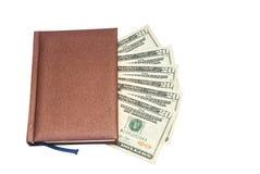 As notas de dólar dos EUA mantêm-se no caderno isolado Imagens de Stock Royalty Free
