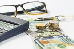 As notas de dólar, pena, moedas, vidros, cartas de negócio estão todas na tabela imagem de stock