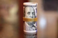 As notas de dólar rolam o dinheiro com a corrente do ouro na boca de franklin Fotos de Stock