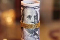 As notas de dólar rolam o dinheiro com a corrente do ouro na boca de franklin Imagem de Stock Royalty Free
