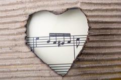 As notas musicais e o coração dados forma queimaram-se fora de um cartão Fotografia de Stock Royalty Free