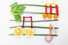 As notas musicais fizeram dos vegetais e dos frutos no branco fotos de stock royalty free