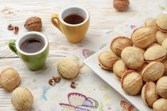 As nozes dão forma a cookies caseiros doces com enchimento do leite condensado do doce e a porcas na placa branca no fundo de mad fotografia de stock