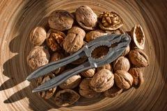 As nozes em um prato de madeira com as pinças para rachar, a parte superior vie Imagem de Stock Royalty Free