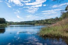 As nuvens brancas bonitas contra o céu azul são espelhadas na água Fotografia de Stock