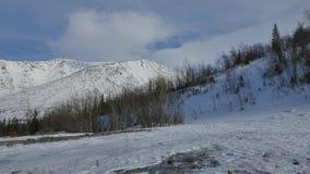 As nuvens brancas bonitas voam sobre as montanhas cobertas com a neve filme