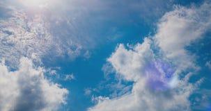 As nuvens brancas que voam no céu azul com sol irradiam Feixes de Sun Lapso de tempo vídeos de arquivo