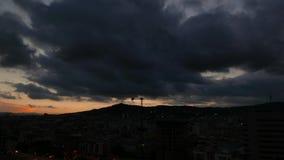 As nuvens da arquitetura da cidade e de chuva do por do sol de Barcelona correm sobre a cidade, tempo-lapso video estoque