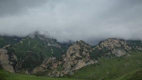 As nuvens de chuva cobrem lentamente as inclinações de montanha rochosos o verde da luxúria da inclinação local dos prados das mo vídeos de arquivo
