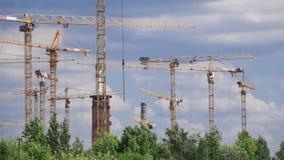As nuvens do verão e o construcrion múltiplo cranes o lapso de tempo da lente teleobjetiva 4K filme