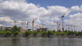 As nuvens do verão e o construcrion múltiplo cranes o lapso de tempo largo da lente 4K vídeos de arquivo