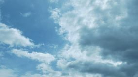 As nuvens escuras movem-se através do céu azul vídeos de arquivo