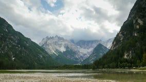 As nuvens estão movendo-se sobre os picos das montanhas alpinas e de um lago da montanha Lapso de tempo video estoque