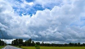 As nuvens grandes e a estrada no campo, travam terrível Fotos de Stock Royalty Free