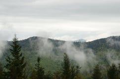 As nuvens misturaram com a névoa e o flutuador após as montanhas fotos de stock