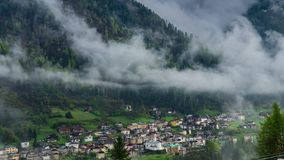 As nuvens movem-se sobre o vale da montanha e a vila alpina video estoque